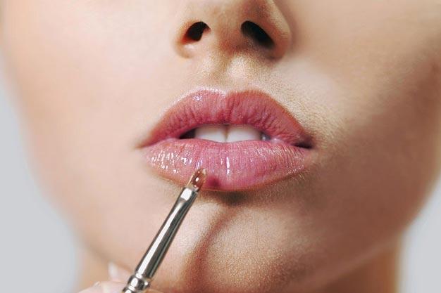 Девушка наносит блеск для губ
